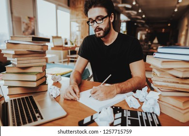 Concept of Young Text Writer Working Indoors. Handsome Hardworking Screenwriter Scenarist Sitting at Table Near Two Big Stacks of Books Writing Article, Novel, Play on Paper Sheets.