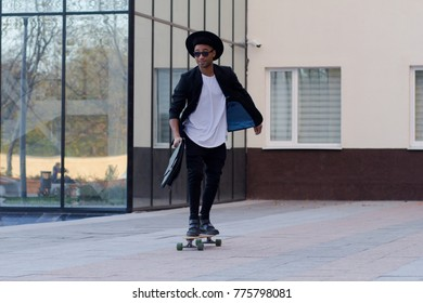 Concept of young,fast and mobile manager. Funny buisinessman on skateboard in black suit.