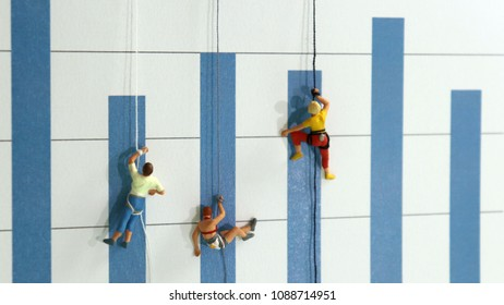 The miniature climbers use a rope to climb the blue bar graph. The concept of youth dreaming of social success.