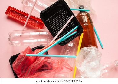 The concept of zero pollution and eco-friendly lifestyle acute social problems. heap of plastic disposable packaging and plastic cocktail straws on a pink background