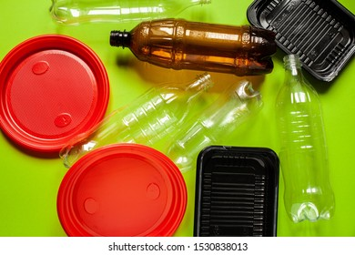 The concept of zero pollution and eco-friendly lifestyle acute social problems. heap of plastic disposable packaging and disposable tableware on a green background