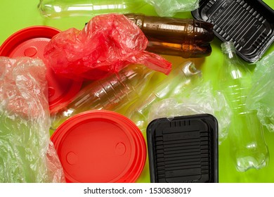 The concept of zero pollution and eco-friendly lifestyle acute social problems. heap of plastic bottles and bags and disposable tableware on a green background