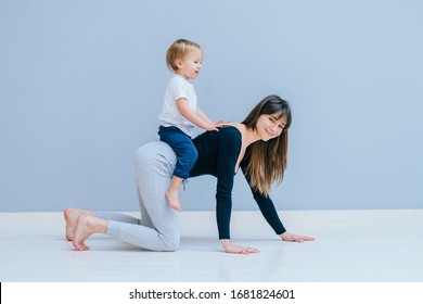Conception of motherhood youth and energy. Sportive woman in a neutral cat cow pose. mother workout an play together with her baby over gray wall background. Crawl, entertain, caressing, amuse concept