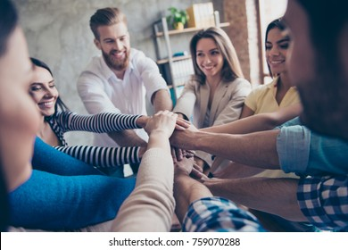 Conception of successful teambuilding. Cropped close up photo of partners putting their hands on top of each other at the workstation, wearing casual clothes, smiling