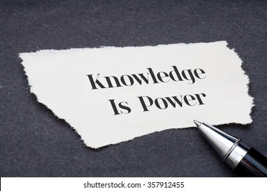 Concept:Knowledge is power written on torn paper with black background and pen