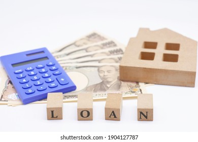 Concepts about mortgages, debt, and family finances. Wooden model of a house. White background.