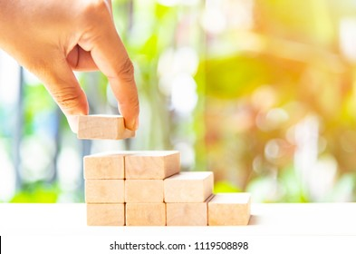 Concepts of building a staircase and step up of wooden pegs for another entrepreneur to climb up the ladder of success.Two finger hold block wood for close project.