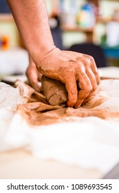 Concepts of Ceramist in Workshop. Closeup of Working  Hands of Male Potter Professional Making a Clay Lump on Workbench in Studio. Vertical Shot