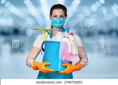 Die Konzepte der Reinigung und Desinfektion. Eine Reinigungsfrau in einer Maske steht auf einem verschwommenen Hintergrund mit Reinigungsmitteln.