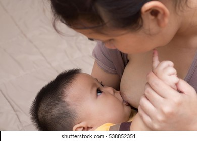 Concepts of lactation and breastfeeding.Asian boy sucking from the breast milk of mothers.Baby feeds on mother's breasts milk