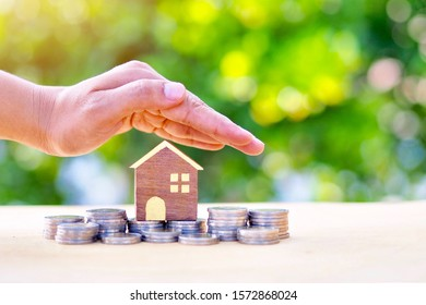 Concepts of protecting and helping the family and family debt problems. (There are hands protecting the pile of coins on the white wooden floor and the house model is placed together.)