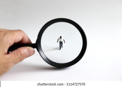Concepts of racial and social prejudice. A miniature man and a magnifying glass.
