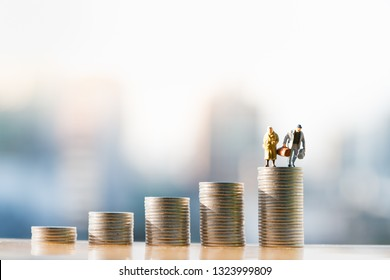 Concepts of retirement planning and finanacial. Miniature people: Old couple figure standing on top of coin stack.