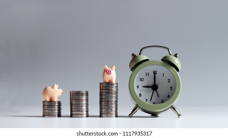 Concepts for savings and financing planning. The small pink pig on top of pile of coins with an alarm clock.