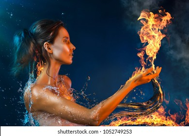 Conceptual art photography of a beautiful asian girl surrounded by burning water splashes holds on her hand fire flame. Copy space. Shining makeup vanguard style. Advertising and commercial design.