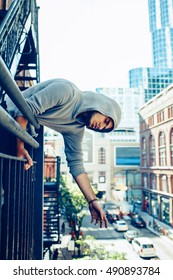 Conceptual art portrait of beautiful handsome pensive sad tired gothic young middle east brunette man with beard in hoodie, standing on staircase in city urban looking down on street