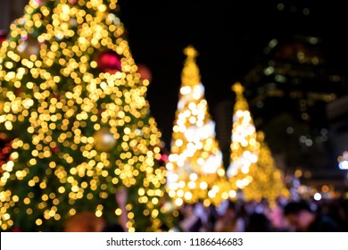 Conceptual background image of defocused abstract Christmas Tree on city street at night