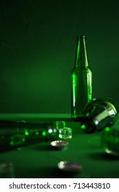Conceptual beer background. Green beer bottles with ice cubes and lids on a green background
