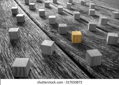 Conceptual Brown Wooden Block Surrounded by Other Blocks in Monochrome on Top of a Rustic Table.
