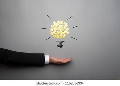 Conceptual bulb drawing with yellow scattered puzzle pieces over open businessman hand on gray background.
