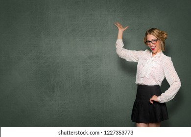 Conceptual business and education, teacher standing by blank blackboard with smile, copy space card