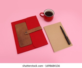 Conceptual business image of a red book or tablet case with a cardboard covered notebook mock up, a pen and a red mug full of coffee, flat lay on pink background