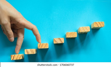 conceptual businessman fingers make big step on wooden blocks to succes and achievment by  strategy(by skip one).
