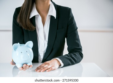 Conceptual Businesswoman in Black and White Suit, Sitting at the Table with a Sky Blue Piggy Bank on her Hand, Captured Close up.