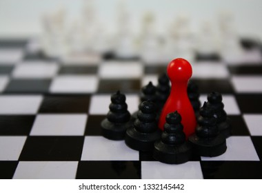 Conceptual chess pieces with red ludo figure like a leader of game in black group of pawns
