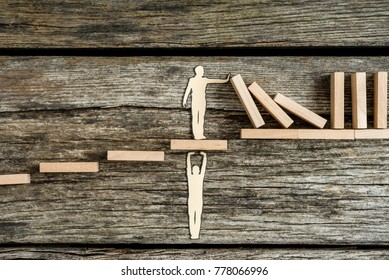 Conceptual close-up of the silhouette of a paper man helping other with support while stopping the negative domino effect of wooden blocks.
