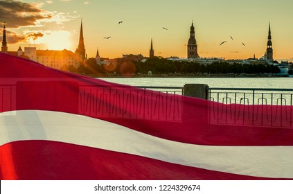Conceptual collage image symbolizing 100 years of Latvian State Independence.  Ancient buildings of Riga - the capital of Latvia known by unique Gothis architecture, Flag of Latvia as background