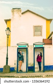 conceptual communication two people on public phone booth male and female