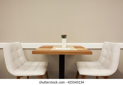 Conceptual composition with one small table and two white armchairs, empty wall in background. Simple but symbolic.