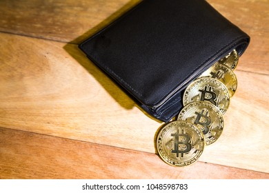 Conceptual cryptocurrency bitcoin with wallet on wooden table