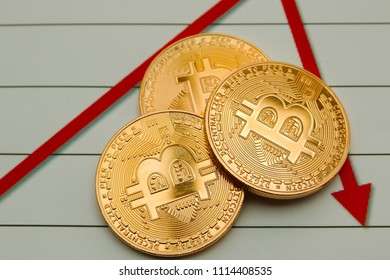 Conceptual cryptocurrency bitcoins on a graph background depicting a fall