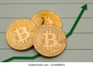 Conceptual cryptocurrency bitcoins on a graph background depicting a rise