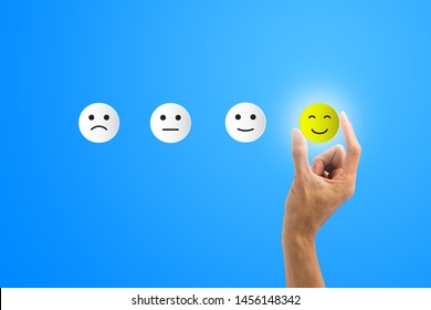Conceptual the customer responded to the survey. The client using hand choose happy face smile icon on blue background.Depicts that customer is very satisfied. Service experience satisfaction concept.