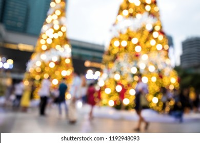 Conceptual defocused Christmas decoration and crowd of people on city street at night