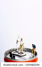 Conceptual diorama image of miniature figures playing golf on the top of a drinks can