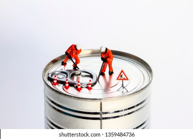 Conceptual diorama image of miniature figures trying to prise open a tin can - Shutterstock ID 1359484736