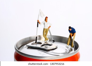 Conceptual diorama image of a miniture figure couple playing golf on a drinks can