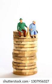 Conceptual diorama image of a miniture figure retired couple sat on a stack of pound coins