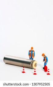 Conceptual diorama image of waste management consisting of miniture figure workmen looking at a battery