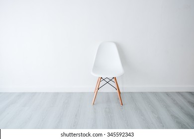 Conceptual Empty White Wooden Leg Chairs with white wall and gray wooden floor and copyspace
