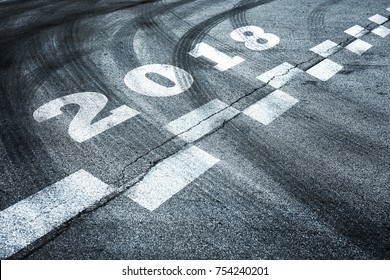Conceptual fast start to the New Year. Number 2018 with abstract line mark on the asphalt road with tires tracks.
