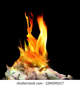 Conceptual finance image of burning pile of money, dollar and euro bills, with fire flames in black background