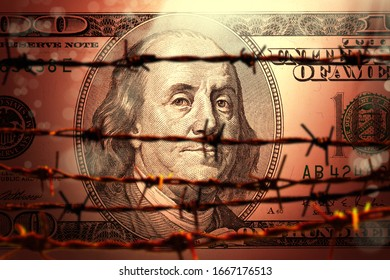 conceptual finance image of close up one hundred dollar bill and barbed wire fence