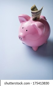 Conceptual financial image with a high angle view of a pink ceramic piggy bank with focus to the coin slot on its back over a grey background with copyspace