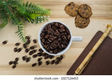 Conceptual Flat-lay of coffee bean, cookies, cinnamon & notebook on wooden background