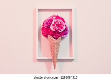 Conceptual gift composition. Pink carnation in ice cream cone arranged in frame. Pink background.
